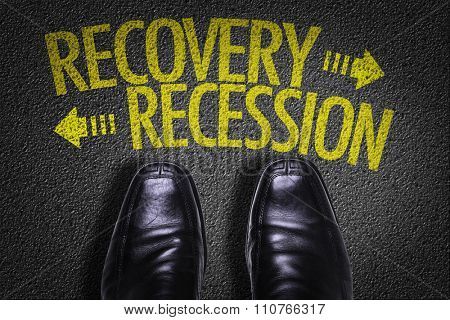 Top View of Business Shoes on the floor with the text: Recovery - Recession