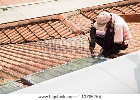 Worker Fixing Solar Water Heater On Roof During Maintenance