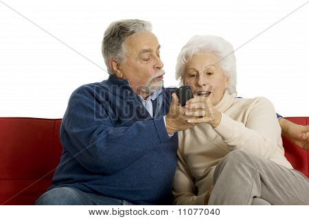 elderly couple on the sofa with television remote control