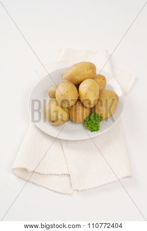 plate of raw potatoes on white place mat