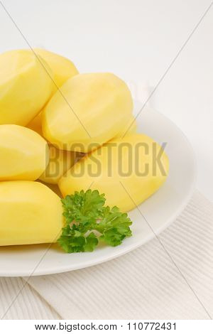 plate of peeled potatoes on white place mat