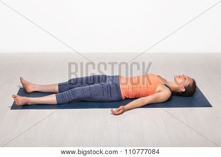 Beautiful sporty fit yogini woman relaxes in yoga asana Savasana - corpse pose in studio