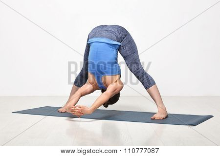 Beautiful sporty fit woman practices Ashtanga Vinyasa yoga asana Prasarita padottanasana C - wide legged forward bend C