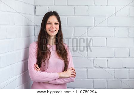Beautiful Woman Stands On A Brick Background