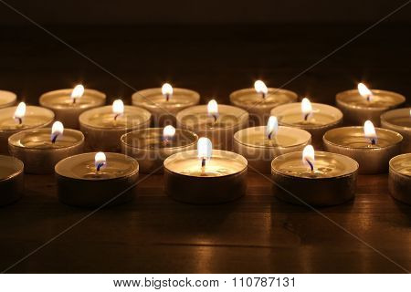 Blazing candles arranged in alignments on brown toned wooden table