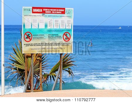 SAINT-PAUL, REUNION ISLAND, FRANCE - NOVEMBER 11, 2015: Notice board with information about danger - risk of sharks. Swimming, snorkeling and surfing prohibited on all Reunion beaches.