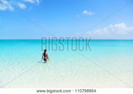 Beach holiday person swimming in blue ocean. Sexy bikini woman relaxing enjoying her tropical vacation in the Caribbean in a paradise destination with perfect turquoise water and white sand.