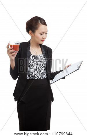 Asian Business Woman With Clipboard And  Tomato Juice