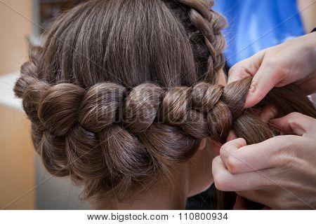 weaving braids brunette in a hairdressing salon