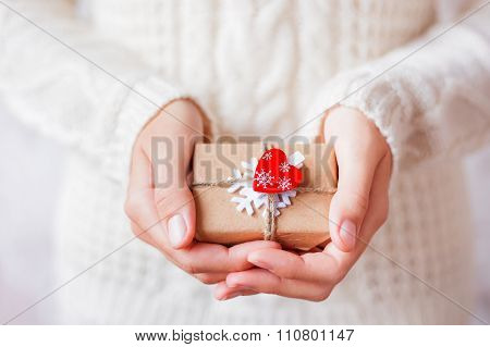 Woman In Knitted Sweater Holding A Present. Gift Is Packed In Craft Paper With Snowflake and Heart