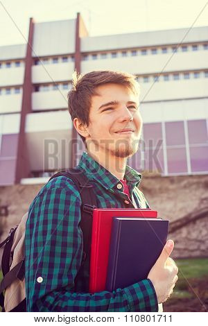 University.Smiling young student man holding a book and a bag on a university background