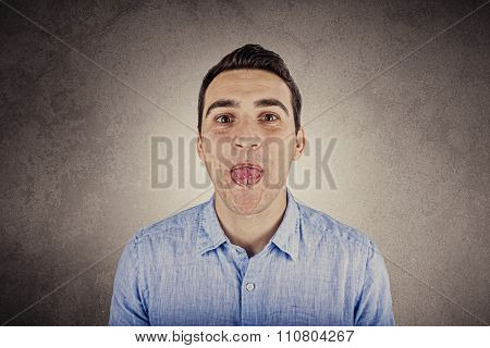 Portrait of a young happy man showing tongue over white background.Confident student showing tongue.