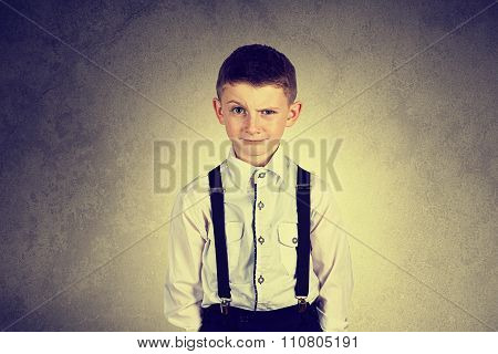 Funny emotionof little boy young man with a raised eyebrow wearing costume with braces
