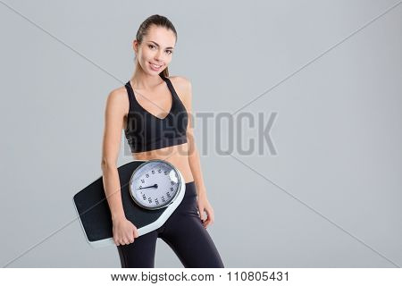 Beautiful smiling young fitness woman in tracksuit holding weigh scale over grey background