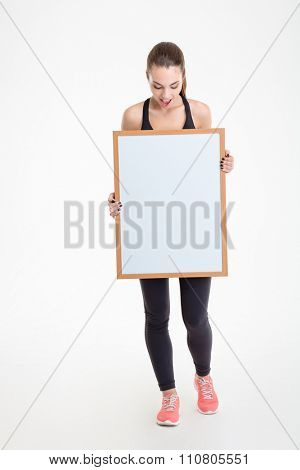 Pretty excited fitness girl in sportwear holding blank board in front of herself and looking on it over white background