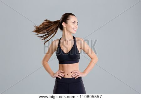 Positive cheerful young fitness woman warming up and turning her head over grey background