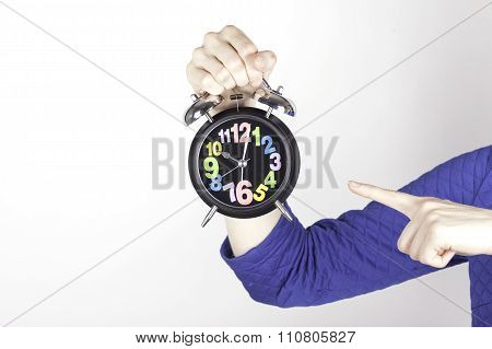 Human index finger pointing at alarm clock, on white background.