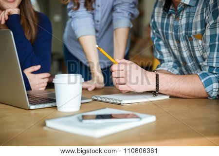 Closeup of students in casual clothes studying and using laptop together