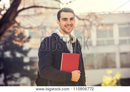 University.Smiling young student man holding a book and a bag on a university