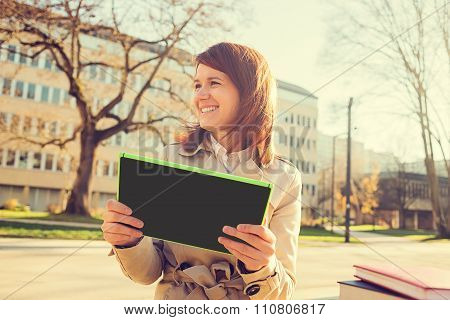 Smiling young woman student taping on tablet using tablet in campus university