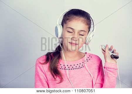 Little girl enjoying music in headphones at home relaxing.