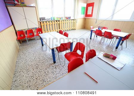 Nursery Classroom With School Desks And Small Red Chairs