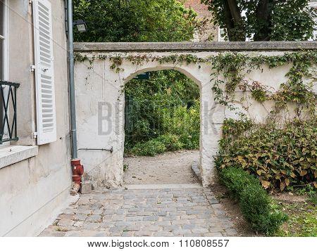 Arched Door In Garden Wall At Renoir Gardens Of Musee De Montmartre, Paris
