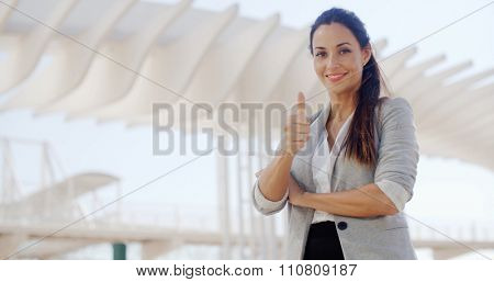 Motivated young businesswoman giving a thumbs up gesture of success and approval as she stands outdoors on a waterfront promenade