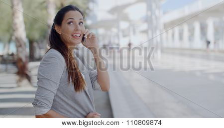 Close up upper body of a pretty relaxed young woman sitting talking on her mobile phone in an urban environment with a happy smile of pleasure.