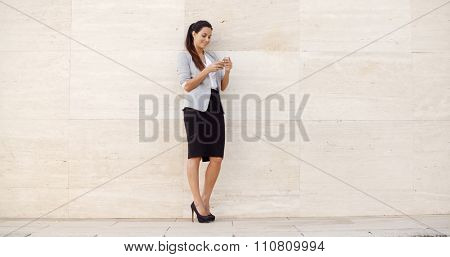 Pretty young woman standing leaning against a neutral cream colored wall with copyspace on either side checking her mobile phone for messages