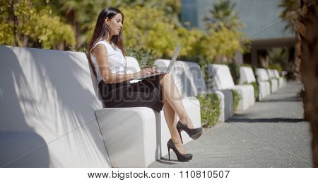 Attractive young business woman sitting on a park bench enjoying the sunshine working on her laptop computer  side view
