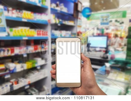 Hand With Smartphone On Blurred In Pharmacy