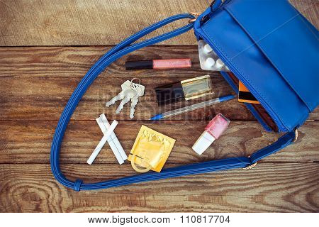 Things from open lady handbag. Cosmetics, accessories, birth control pill, cigarette and condom