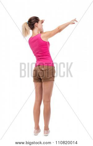 Back view of  pointing woman. beautiful girl. Rear view people collection.  backside view of person.  Isolated over white background. Blonde in brown shorts saw something interesting on the left.