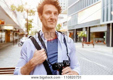 Happy male tourist walking in city with camera