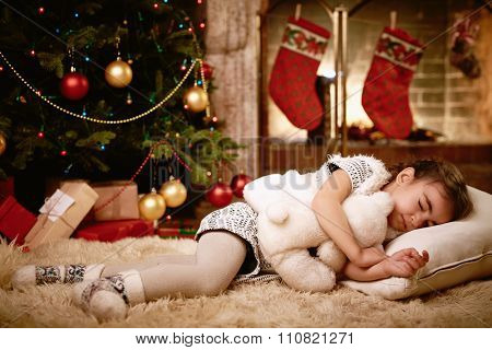 Cute girl with teddybear sleeping by fireplace on Christmas evening
