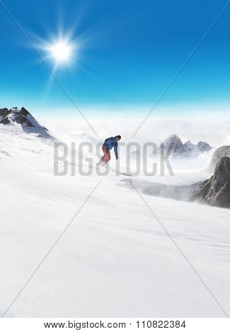 Snowboarder man running down on piste at high speed. Alpine mountain masive on background