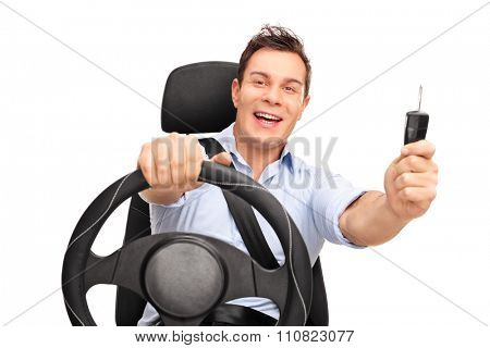 Young man sitting on a car seat fastened with seatbelt and holding a car key isolated on white background