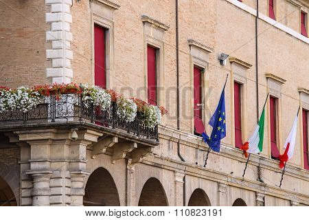 Facade Of Rimini City Hall With Flags And Flowers On Cavour Square In Rimini, Italy