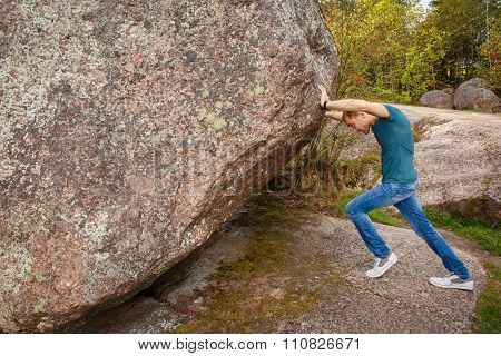 Man With Backpack Pushing A Huge Stone