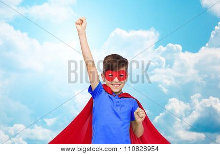 carnival, childhood, power, gesture and people concept - happy boy in red superhero cape and mask showing fists over blue sky and clouds background