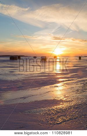 Ice fishing with lens flare at sunset along the shores of rural Prince Edward Island.