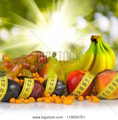 Different Fruits And Centimeters On A Green Background
