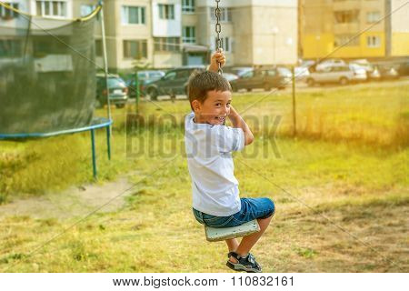 Little Boy Having Fun On A Swing Outdoor