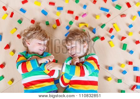 Two little children playing with colorful wooden blocks indoor