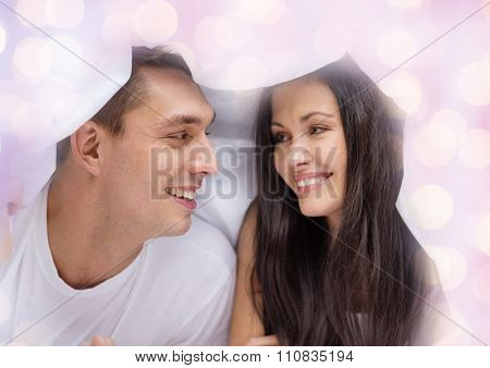 people, love, relations and bedtime concept - happy couple under blanket in bed over lights background