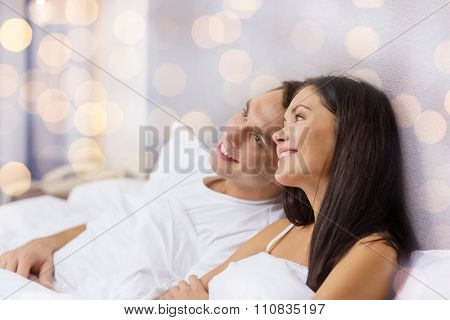 hotel, travel, relationships, and happiness concept - happy couple dreaming in bed over lights background