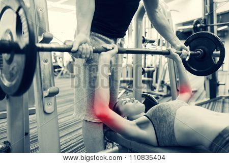 sport, fitness, weightlifting, sports injury and people concept - young woman and personal trainer with barbell flexing muscles in gym
