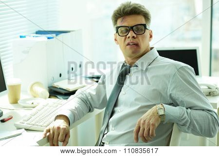 Businessman with bruised face sitting at his workplace