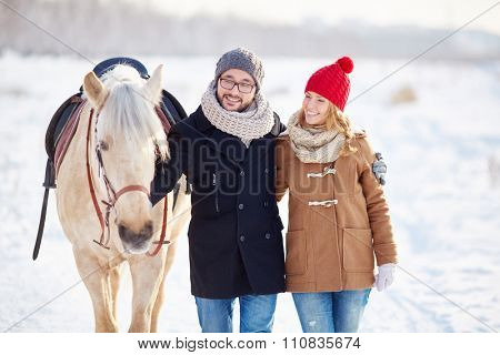 Young couple walking with horse in winter day